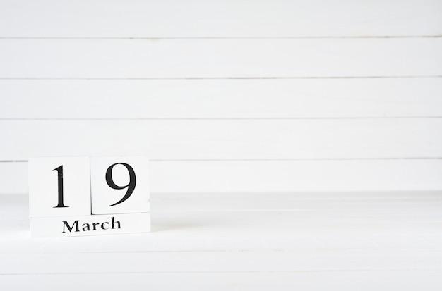 19 mars, jour 19 du mois, anniversaire, anniversaire, calendrier de bloc en bois sur un fond en bois blanc avec espace de copie du texte.