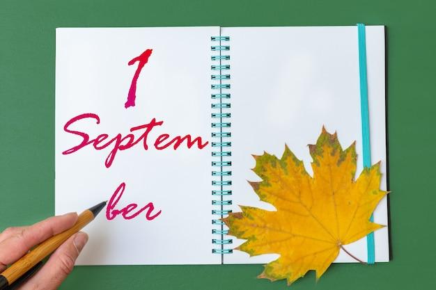 1er jour de septembre. main gauche écrivant la date 1 septembre dans un carnet ouvert avec une belle feuille d'érable naturelle sur fond vert. mois d'automne, concept de jour de l'année.