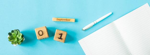 1er septembre sur un calendrier en bois parmi les fournitures pour étudier sur fond bleu