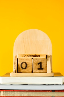 1er septembre sur un calendrier en bois parmi les manuels à étudier sur fond jaune