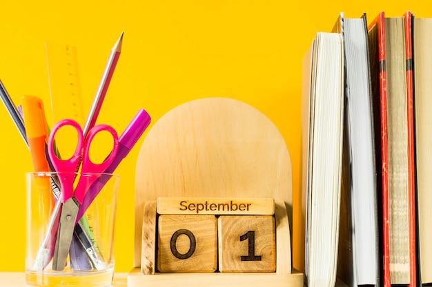 1er septembre sur un calendrier en bois parmi des manuels et des stylos pour étudier sur un fond jaune
