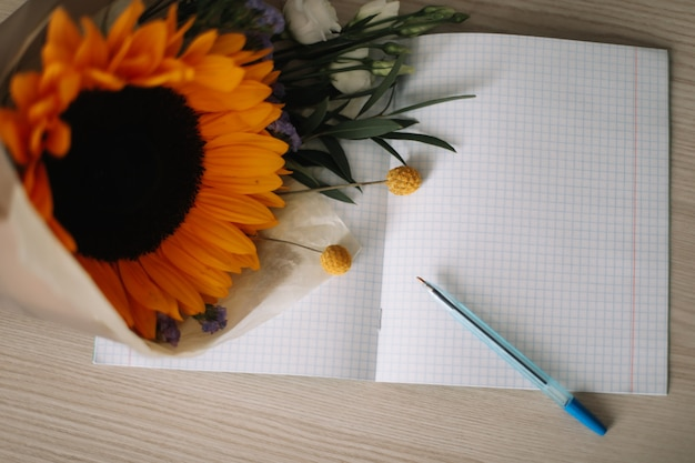1er septembre concept de retour à l'école bouquet avec tournesol et fournitures scolaires sur table