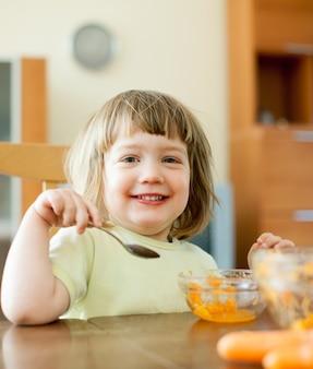 2 ans, l'enfant mange une salade de carottes