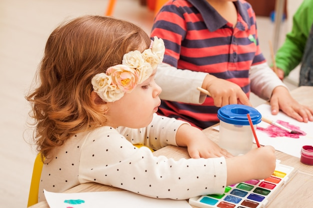 2 ans les enfants apprennent à peindre avec un pinceau et des aquarelles sur papier à la maternelle