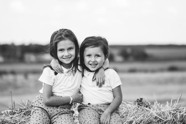 2 ans, fille assise sur une balle de foin dans le champ au coucher du soleil