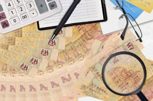 2 factures de hryvnias ukrainiennes et calculatrice avec lunettes et stylo