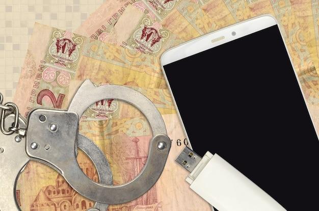 2 factures de hryvnias ukrainiennes et smartphone avec des menottes de police