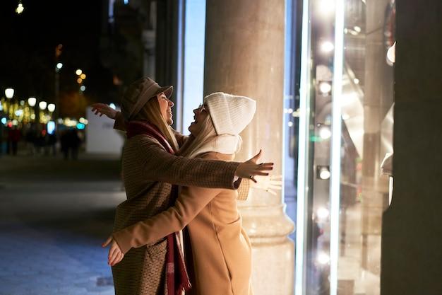 2 jeunes femmes, heureuses et excitées de se revoir, s'embrassent avec enthousiasme.