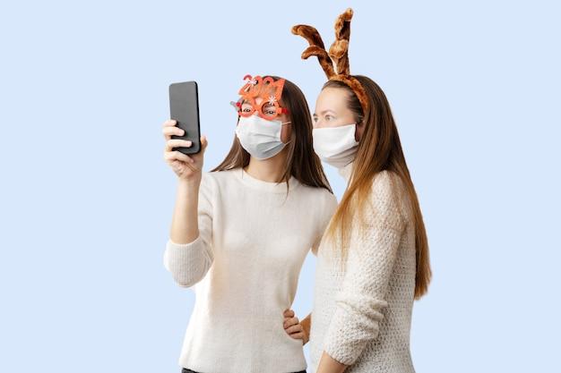 2 jeunes filles ou jeune femme avec bonnet de noel et masque facial faisant appel vidéo en ligne.