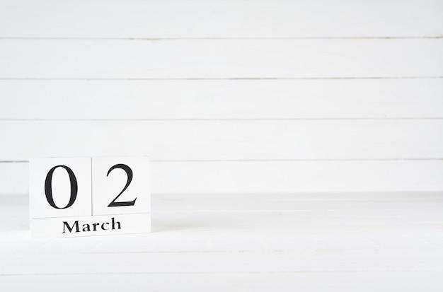2 mars, jour 2 du mois, anniversaire, anniversaire, calendrier de bloc en bois sur un fond en bois blanc avec espace de copie pour le texte.