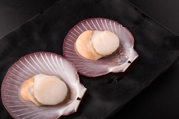 2 pétoncles crus isolés sur un plat noir, gros plan de pétoncles frais pelés.