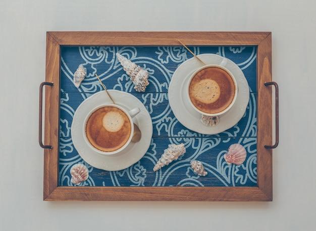 2 tasses de café dans le plateau de service avec des objets décoratifs vue de dessus sur blanc
