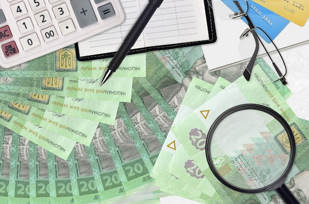 20 factures de hryvnias ukrainiennes et calculatrice avec lunettes et stylo.