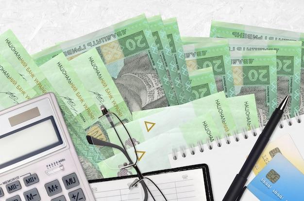 20 factures de hryvnias ukrainiennes et calculatrice avec lunettes et stylo
