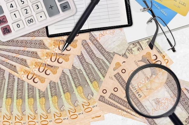 20 factures en peso dominicain et calculatrice avec lunettes et stylo.