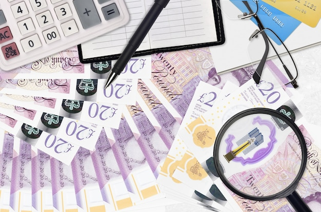 20 livres sterling et calculatrice avec lunettes et stylo. concept de saison de paiement des impôts ou solutions d'investissement. rechercher un emploi avec un salaire élevé