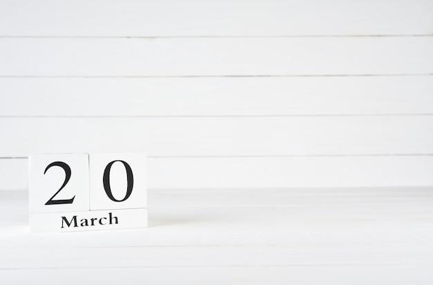20 mars, jour 20 du mois, anniversaire, anniversaire, calendrier de bloc en bois sur un fond en bois blanc avec espace de copie du texte.