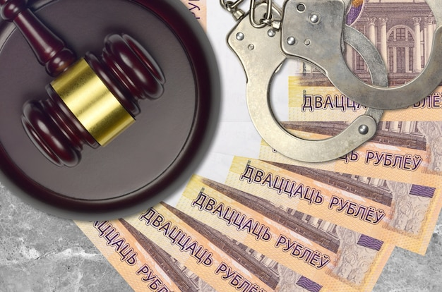 20 roubles biélorusses factures et juge marteau avec des menottes de police sur le bureau du tribunal. concept de procès judiciaire ou de corruption. évasion fiscale ou évasion fiscale