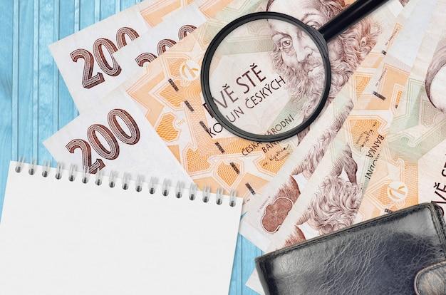 200 billets de couronnes tchèques et loupe avec sac à main noir et bloc-notes. concept de monnaie contrefaite. rechercher des différences dans les détails sur les factures d'argent pour détecter la fausse monnaie