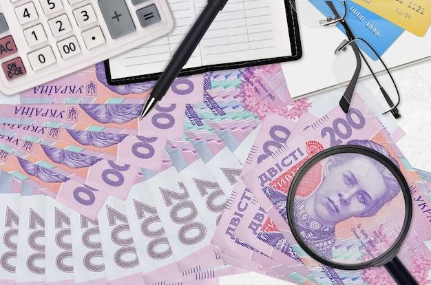 200 factures de hryvnias ukrainiennes et calculatrice avec lunettes et stylo.