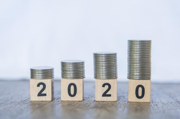 2010 nouvel an, argent et affaires. gros plan d'une pile de pièces de monnaie sur le dessus de jouet numéro de bloc en bois sur la table en bois et blanc.