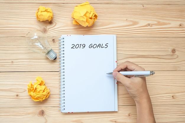 2019 joyeux nouvel an avec un homme d'affaires écrivant avec une ampoule