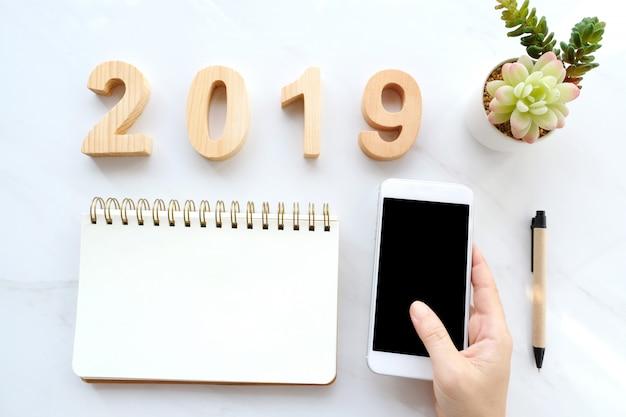2019 lettre en bois, papier vierge et main tenant un téléphone intelligent