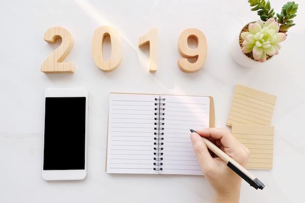 2019 lettres en bois, main qui écrit sur du papier vierge, téléphone intelligent avec écran blanc