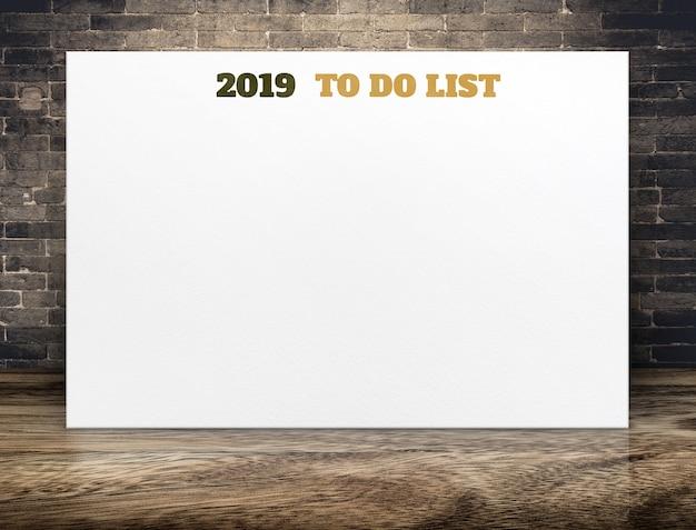 2019 nouvel an à faire la liste sur une affiche en papier blanc sur la salle de plancher en bois brun et mur de briques