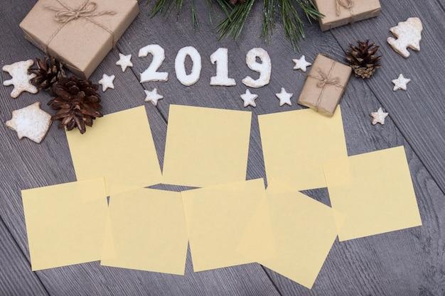 2019 numéros de biscuits avec des cadeaux, sapin, pin sur fond en bois. nouvel an. souhaite un