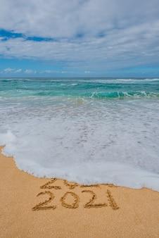 2020 2021 écrit dans le sable avec une vague emportant 2020