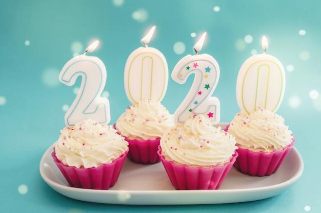 2020 bougies sur cupcakes avec glaçage à la crème fouettée à l'aide de tasses réutilisables en silicone rose