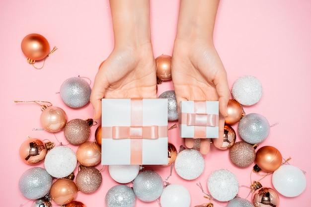 2020 composition du nouvel an. conception de concept de décoration élégante, jouets ronds de sapin de noël, mains tenant la boîte-cadeau sur rose