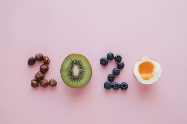 2020, fabriqué à partir d'aliments sains sur fond rose pastel, régime alimentaire et mode de vie de healhty
