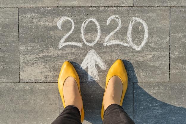 2020, flèche vers l'avant, écrite sur un trottoir gris avec des jambes de femme, vue de dessus