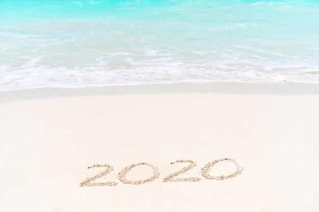 2020 manuscrite sur une plage de sable fin avec une douce vague océanique