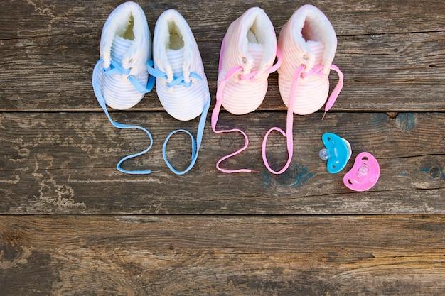 2020 nouvel an écrit lacets de chaussures pour enfants et sucette sur une vieille table en bois. vue de dessus. mise à plat.