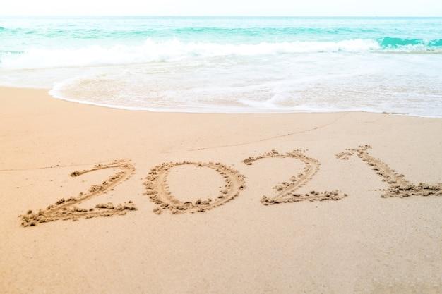 2021 année dessiné à la main sur la plage d'été de sable.