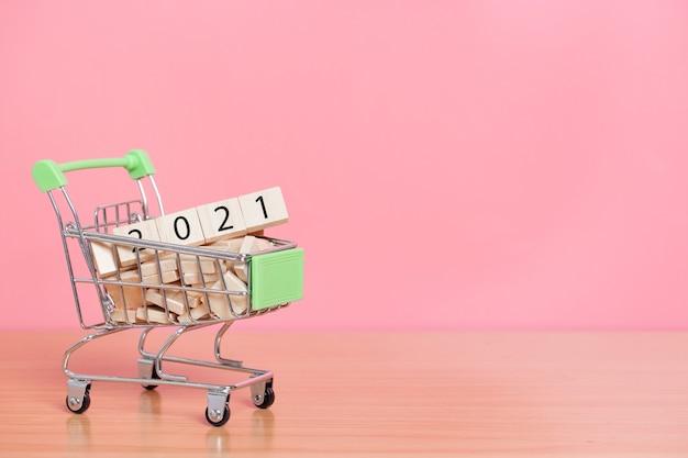 2021 avec cube de bois dans le panier sur fond rose. concept de bonne année.