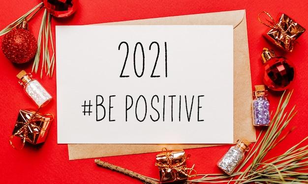 2021 être une note de noël positive avec cadeau, branche de sapin et jouet sur rouge isolé. concept de nouvel an
