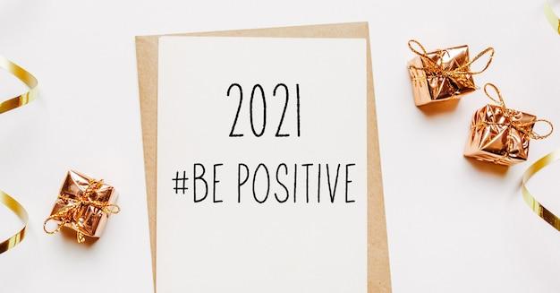 2021 être une note positive avec enveloppe, cadeaux et ruban d'or sur fond blanc. joyeux noël et nouvel an concept