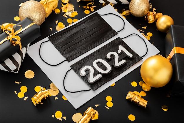 2021 sur masque chirurgical médical noir sur décor de noël.