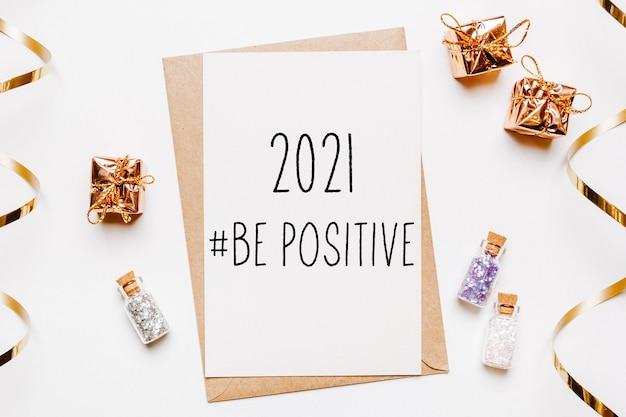 2021 soyez une note positive avec une enveloppe, des cadeaux et des étoiles à paillettes d'or sur une surface blanche. joyeux noël et nouvel an concept
