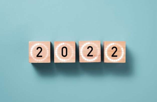 2022 année avec signe de chargement sur bloc de cube en bois avec fond bleu, joyeux noël et bonne année concept de préparation.