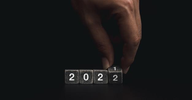 2022 bonne année bienvenue et bannière joyeux noël. retournant à la main des blocs de cubes en pierre noire pour changer l'année 2021 à 2022 sur fond sombre.