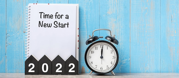 2022 bonne année avec l'heure d'un nouveau départ, réveil rétro noir et numéro en bois.résolution, objectifs, plan, action et concept de mission