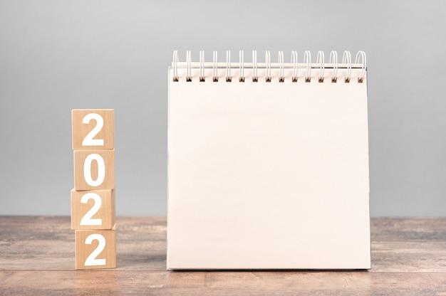 2022 cubes avec un bloc-notes sur une table en bois. plans pour 2022