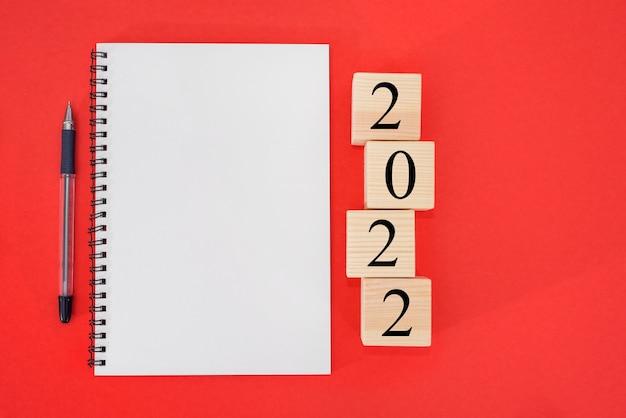 2022 est l'heure d'un nouveau départ plan word et 2022 cubes sur fond rouge
