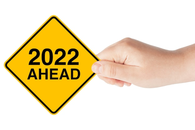 2022 year ahead traffic sign in woman's hand sur fond blanc
