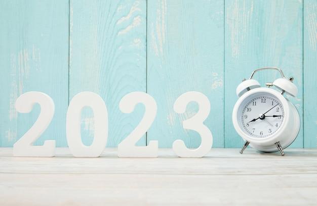 '2023' fait avec des chiffres en plastique et un réveil sur un bois bleu
